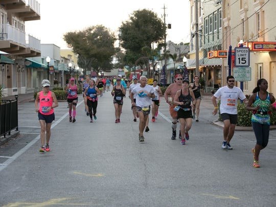 Racers take off at 6:30 am through the deserted streets of downtown Stuart as they run to claim their marathon medal