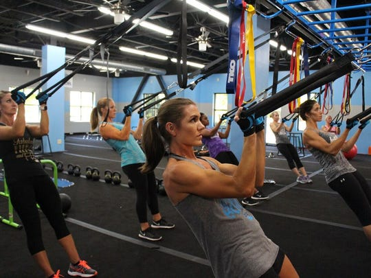 Women work out with ropes at Burn Boot Camp.