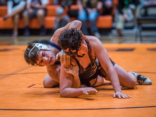 Bloomfield's Avery Scott, left, works against Aztec's Hunter Medina on Saturday at Lillywhite Gym in Aztec.