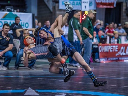 Bloomfield's Levi Whitley, top, takes down Española Valley's Amado Ramirez on Friday at the Santa Ana Star Center in Rio Rancho.