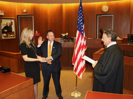 Scott Coffina of Evesham was sworn in as Burlington County prosecutor by Superior Court Judge Ronald E. Bookbinder in Mount Holly in March. Coffina's wife, Kim, holds the Bible.