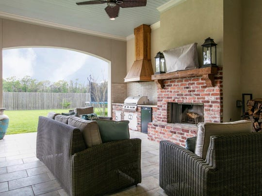 The outdoor living space includes a kitchen and entertainment area.