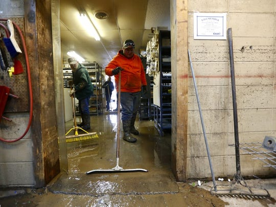 Ryan Reid, right, and Don Hawkins sweep water out of Cawvey's Electric Motor in West Plains. The water mark can be seen on the wall.