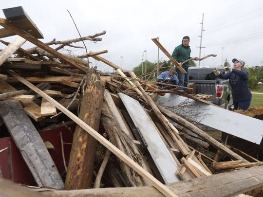 Brendon Knobloch, center, along with Steve and Dora DeClue toss lumber onto the trash pile while volunteering to clean up from the effects of the recent flood in West Plains.