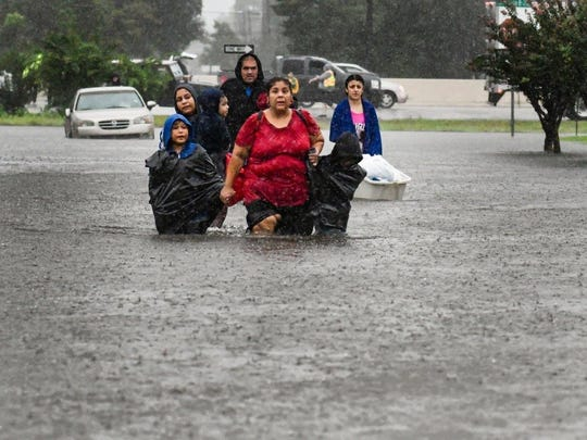 Residents wade through waist high water to get to safety after devastating flooding caused by Hurricane Harvey.