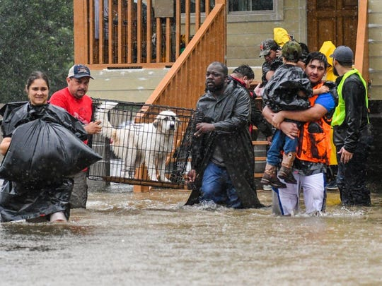 Northeast Houston residents are rescued from flooded homes by Police and volunteers on Monday.