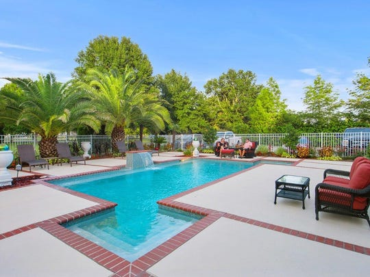 The pool is surrounded by lush landscaping and entertainment space.