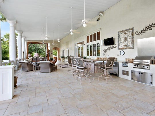 The fabulous veranda inlcudes a full outdoor kitchen and luxurious seating.