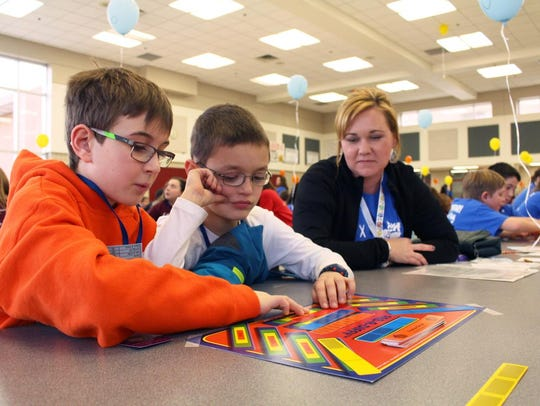 Alex Hotra (left) and Evan Findling of Country Oaks Elementary School in Commerce perform in the math pentathlon under the guiding eyes of parent volunteer Sarah Hammond.