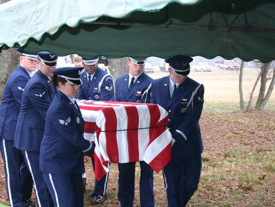 A military honor guard of pall bearers carries the