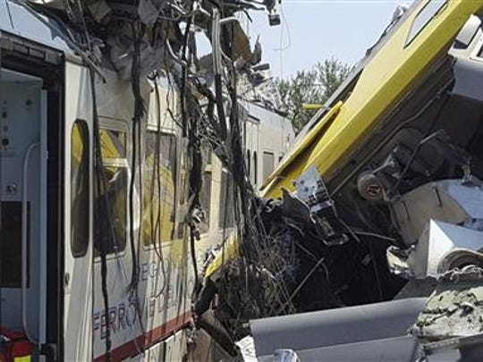 Crumpled wagon cars are seen after after two commuter trains collided head-on near the town of Andria, in the southern region of Puglia, killing at least 12 people, Tuesday, July 12, 2016.