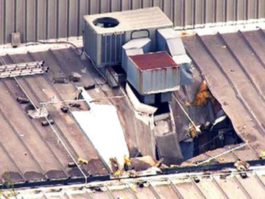 This Monday, April 3, 2017 photo from video by KMOV shows damage to the roof of a laundry business in St. Louis after a boiler exploded at a nearby box company and flew before crashing through the roof. Authorities said several people were killed as a result of the explosion.