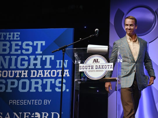 Peyton Manning walks on the stage during Argus Leader