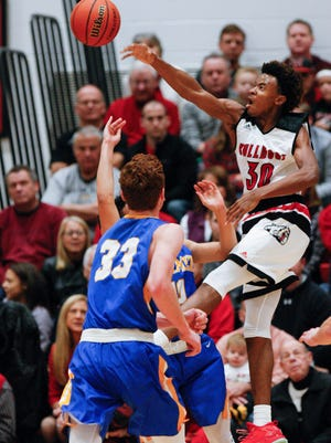 New Albany's Julien Hunter (30) blocks a shot attempt by Carmel during their game at New Albany High School.  New Albany edged Carmel 55-52.Dec. 20, 2016