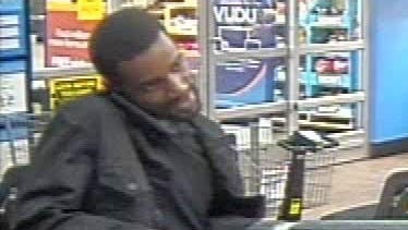 One suspect appeared to be holding a shopping bag and rolled-up carpet while talking on a cellphone.