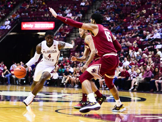 Dwayne Bacon (4) drives for the basket during the first
