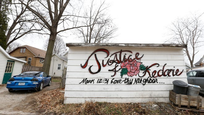 The side of a garage was tagged with a memorial for Kedarie Johnson in the alley where he was found dead March 2 in Burlington, Iowa. Police are continuing to investigate the death as a murder.
