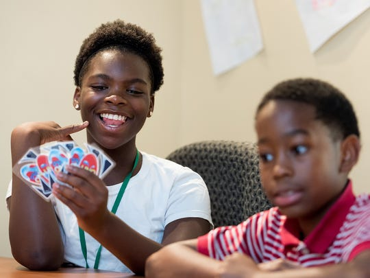 Lorna Barry, 12, and Khalil Thomas, 9, play Uno at the New Horizons Community Center in Wilmington.