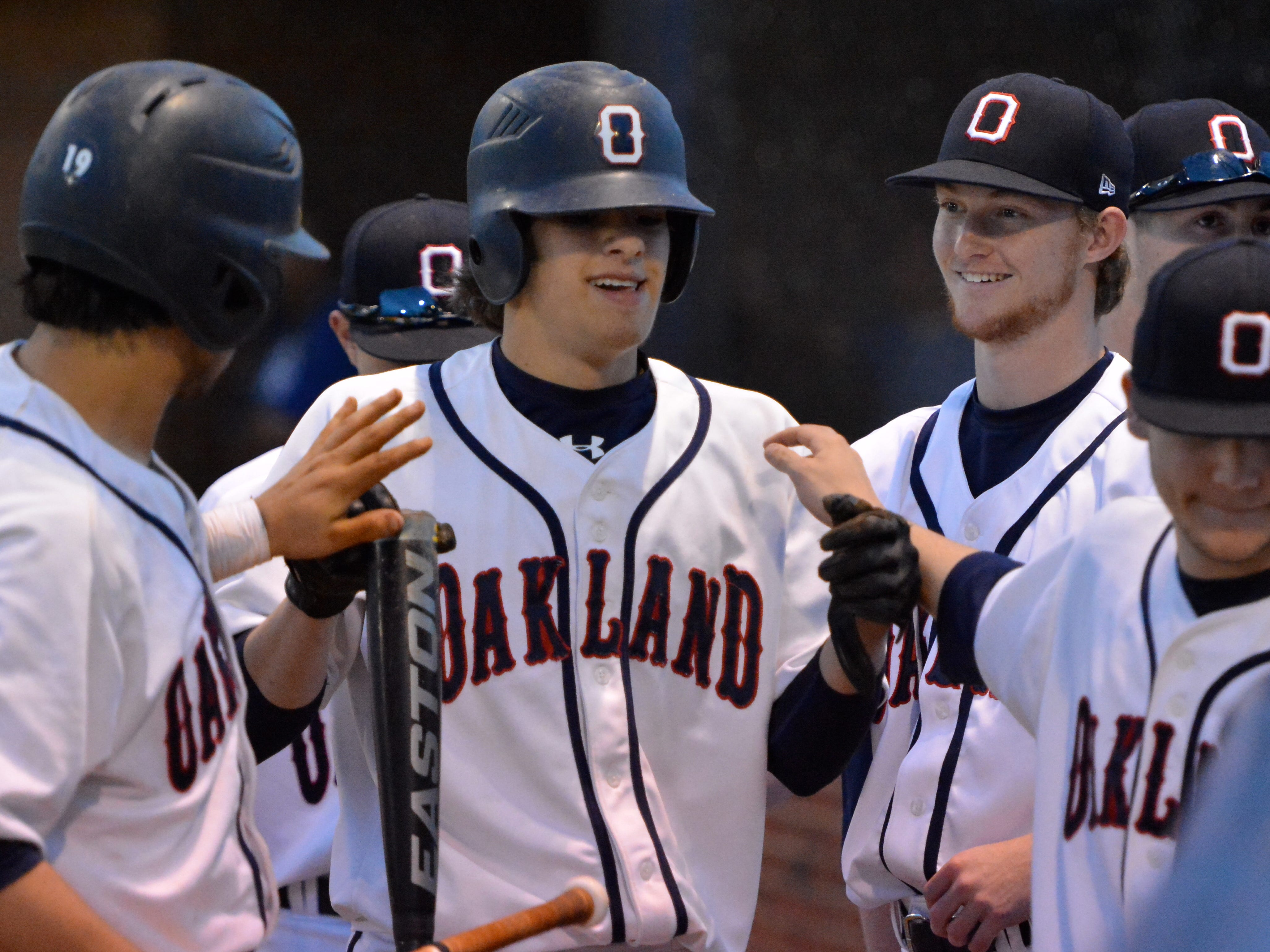 Oakland High catcher Justin Wilson, center, has signed with Lipscomb University to play baseball.
