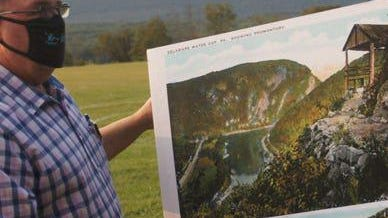 Portland, Pa. Mayor Lance Prator adjusts a reproduction of an old postcard of the Delaware Water Gap on Wednesday, Sept. 16, 2020, prior to a series of speeches by elected officials from 14 New Jersey and Pennsylvania municipalities who are rallying against a NJ Department of Transportation on Interstate 80 which goes through the Delaware Water Gap, seen in the background. The rally was held at the Upper Mount Bethel, Pa., Community Park.