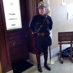 A Rhode Island state trooper stands outside the office of House Speaker Gordon Fox on March 21, 2014.