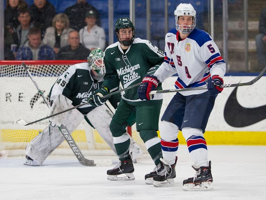 Michigan State goalie Ed Minney (45) and defenseman Tommy Miller (12) face their former team on Dec. 16. At right for the U.S. NTDP Under-18 squad is defenseman Adam Samuelsson (5).