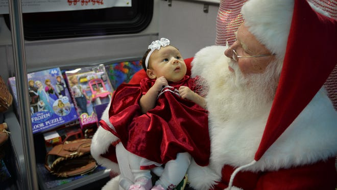 Six-week old Delilah Jayde, daughter of Robin Eye of Lebanon, rests comfortably on Santa Claus' lap surrounded by some of the toys donated for the Lebanon Transit Stuff The Bus event  Friday, Dec. 18, 2015, at the Lebanon Farmers Market. Lebanon Transit offerrf a place for local children to meet with Santa  while collecting toys for the Lebanon County Detachment Marine Corps League Post  525 Toys for Tots program.