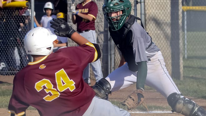 West Allis Nathan Hale catcher Noah Hess sets up to tag West Allis Central''s Jake Fierst at home in the third inning of the Huskies' 7-1 loss to their crosstown rivals at Belich Field, June 17.