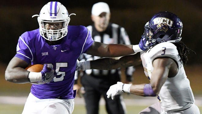 Furman's Antonio Wilcox (25) tries to fend off Western Carolina's Fred Payne (3).