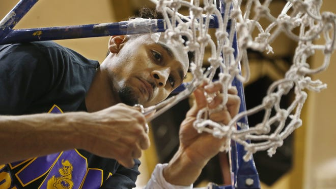 Vijay Blackmon cuts down the nets after Marion defeated Griffith 60-58 in the Class 3A basketball semistate March 23, 2016.