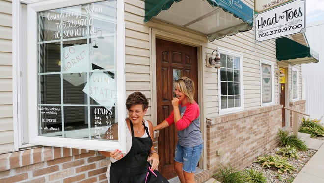 Jill Cloud, left, and Tonya Metzger laugh as they place hand written notes encouraging the Rossville Hornets baseball team in the front window Wednesday, June 14, 2017, at Head to Toes beauty salon, 51 N. Plank Street in Rossville. Rossville will play Lanesville in the Class A baseball state finals Saturday in Indianapolis. The women said they are closing the salon on Saturday to attend the game.