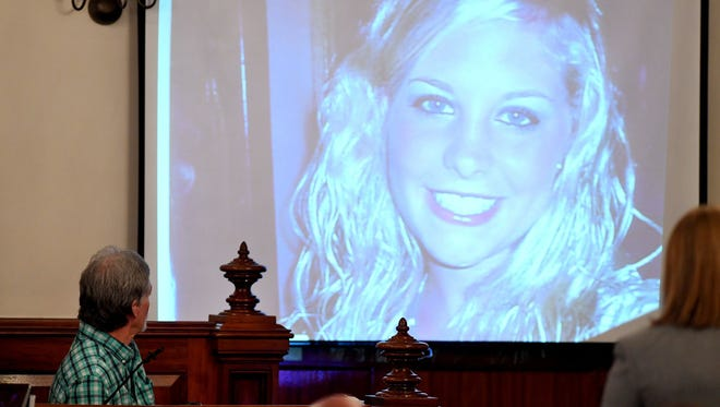 Dana Bobo, left, looks up at a photo of his daughter, Holly Bobo, presented on a projector during his testimony Monday, Sept. 11, 2017, in Savannah, Tenn.