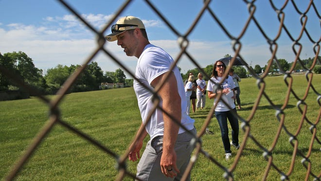 Jason Seaman, a Noblesville (Ind.) West Middle School science teacher, walks back to his seat after talking to his students over a fence Monday, May 28, 2018. His appearance at the Indiana High School Athletic Association baseball championships was the first time his students saw him since a school shooting May 25, 2018. Seaman intervened to stop the shooter from shooting more students.