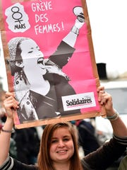"A woman carries a sign reading ""Women Strike!"" during a demonstration march on March 8, 2017 in Toulouse, as part of International Women's Day."