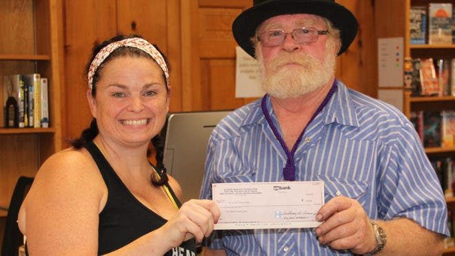 """The director of the library, Amanda Doherty, pictured accepting a $200 check from Barry Leach, the Worshipful Master of the Mount Pulaski Masonic Lodge #87. Doherty said the money would go to their youth program, """"Inspiring Learning"""" which is a non-fiction activity for the youth of the community."""