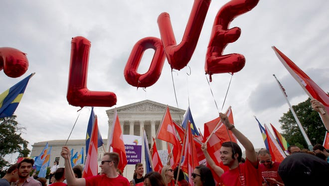 "Balloons spell out the word ""love"" over the Supreme Court in Washington on June 26, 2015, after the court declared that same-sex couples have a right to marry anywhere in the U.S."