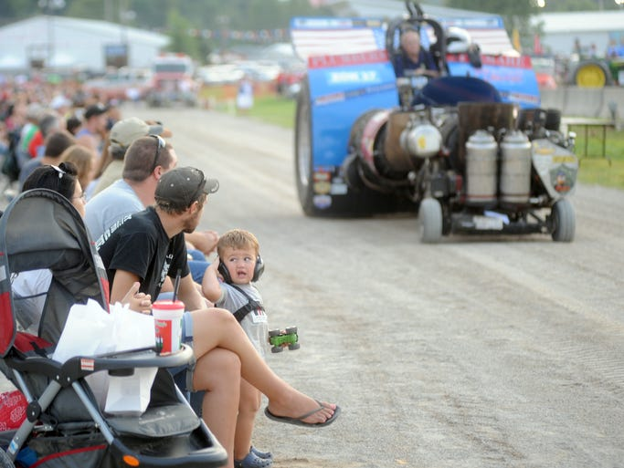 Boone Rayner, 1, looks to his family as Don Deane of Trafalgar, Ind. drives past in his modified class vehicle. Boone came to the National Tractor Pullers Association Truck & Tractor Pull with his parents Corrie and Josey Rayner of Blue Rock. Thirty-six vehicles took part in the event on the opening night of the Muskingum County Fair.