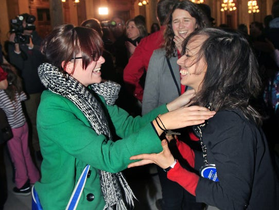 Giovanna Kravjo, right, who identifies as bi-sexual, celebrates with other opponents of HJR-3, including Lindsey Smith, left, as Caroline Wickes looks on (all three are Indiana University students) after the Indiana House of Representatives voted 52-43 to strike the second sentence from the proposed constitutional amendment on marriage during second reading in the House at the Indiana Statehouse in Indianapolis on Monday, January 27, 2014. If the General Assembly approves the measure as altered, civil unions would not be explicitly banned and the proposed constitutional amendment would not go to voters this November.
