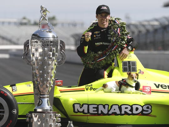 Simon Pagenaud, of France, winner of the 2019 Indianapolis 500 auto race, poses with his dog Norman during the traditional winners photo session at the Indianapolis Motor Speedway in Indianapolis, Monday, May 27, 2019. (AP Photo/Michael Conroy) ORG XMIT: NAA109
