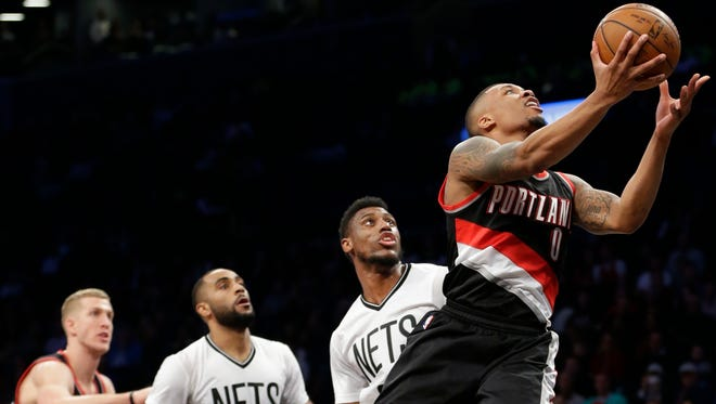 Portland Trail Blazers' Damian Lillard (0) drives past Brooklyn Nets' Thaddeus Young, second from right, and Wayne Ellington, second from left, during the first half of an NBA basketball game Friday, Jan. 15, 2016, in New York.