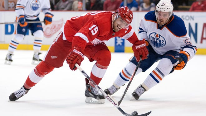 Edmonton Oilers center Anton Lander, right, attempts to poke away the puck from Detroit Red Wings center Riley Sheahan at Joe Louis Arena.