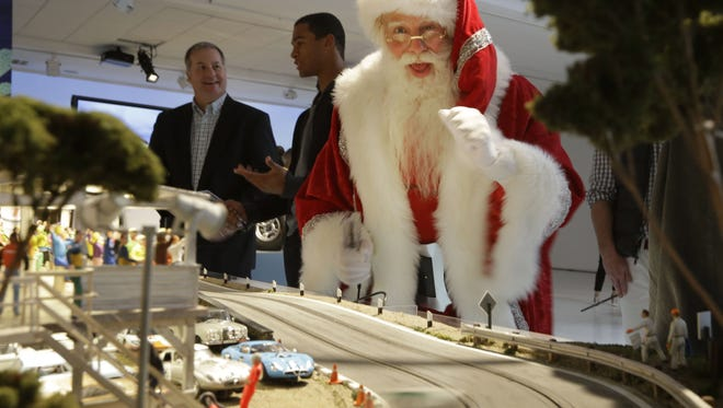 Santa Claus plays with the Slot Mods USA Ultimate Slot Car Raceway during the unveiling of the Neiman Marcus Christmas Book, Tuesday, Oct. 7, 2014, in Dallas. The cost of the 1:32 scale model race track is $300,000. (AP Photo/LM Otero)