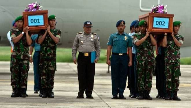Indonesian military personnel carry coffins of victims recovered from AirAsia Flight 8501 upon their arrival at the military air base in Surabaya.