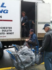 Members of Legion Post 621 in St. Augusta unload gifts purchased with grant money for the St. Cloud VA Health Care System.