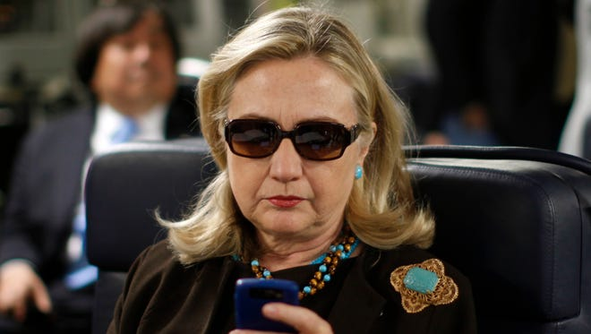 Then-Secretary of State Hillary Rodham Clinton checks her Blackberry from a desk inside a C-17 military plane upon her departure from Malta, in the Mediterranean Sea, bound for Tripoli, Libya.