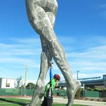 """In this photo taken Wednesday Oct. 19, 2016, a woman poses beneath a 55-foot nude statue in San Leandro, Calif. The statue of a naked woman is stirring controversy and a lot of conversation. City officials and the sculptor of the steel nude, which was unveiled this week across from San Leandro's main commuter train stop, say they want to draw attention to """"feminine energy."""" Critics say the 13,000-pound towering nude is not appropriate public art. (AP Photo/Jocelyn Gecker)"""