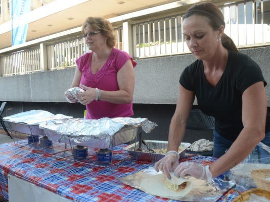 ANI Dinner on the Bricks Hot Chicks BBQ owner Tammy Gilchrist (right) makes a pork and cole slaw wrap as Denise Good takes an order at Dinner on the Bricks Thursday, April 30, 2015 in downtown Alexandria. Hot Chicks BBQ was among the food vendors participa