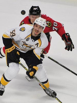 Predators defenseman Roman Josi and Blackhawks left wing Dennis Rasmussen look for the puck during the first period in Chicago on Tuesday night.