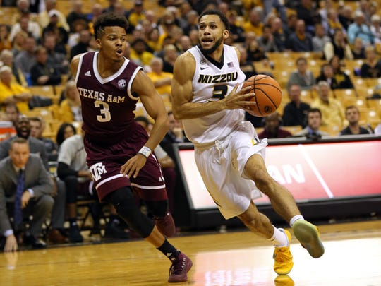Missouri Tigers guard Kassius Robertson dribbles the ball as Texas A&M Aggies guard Admon Gilder defends in the first half at Mizzou Arena.