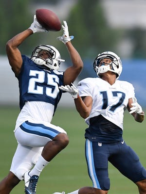 Titans cornerback Adoree' Jackson (25) pulls in an interception over wide receiver Jonathan Krause (17) during a night training camp practice at Saint Thomas Sports Park Monday, Aug. 7, 2017 in Nashville , Tenn.